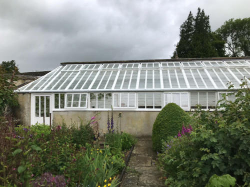 White-painted-bespoke-greenhouse-with-porch-edge-front