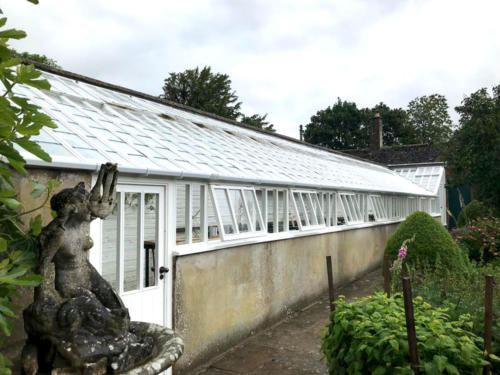 White-painted-bespoke-greenhouse-with-porch
